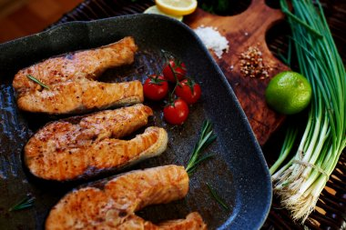 There are several salmon steak on the grill pan