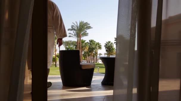 ein Mann in weißem Gewand und mit Tablet verlässt den Raum auf der Terrasse mit Meerblick, setzt sich in einen Sessel und blättert in der Tablette, Vorhänge im Vordergrund, Palmen im Hintergrund