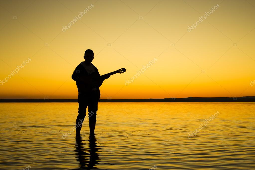 Turkey, the Salt Lake at sunset silhouette of a man playing guitar day