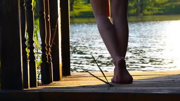 lány sétál egy fából készült mólón a lábujjak. lány léptető lábujjak óvatosan a fa padlón. Megy a vízbe. szél a víz képez hullám. a nap sugarai hullanak a lábuk .