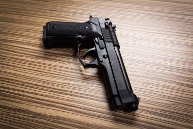 black gun on wooden desk