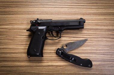 Gun on wooden desk, with knife stock vector