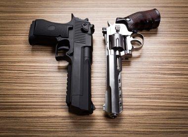 two guns on wooden desk