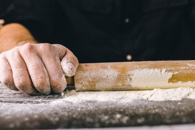 Hands baking dough with rolling pin