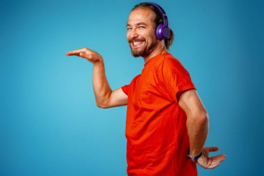 Handsome middle-aged man listening to music with blue headphones