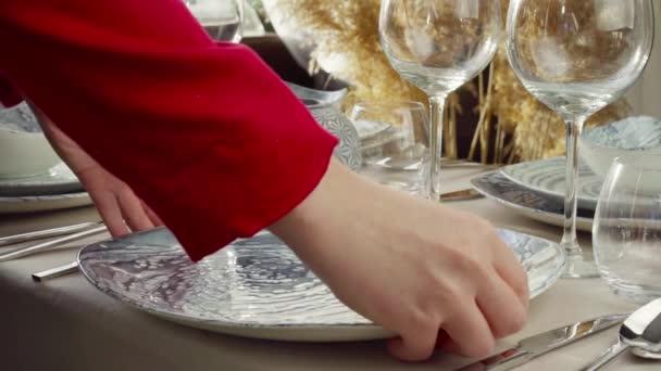 Großaufnahme vom gedeckten Tisch der Frau. Hausfrau oder Kellnerin legt Teller auf den Esstisch