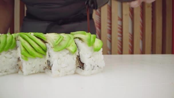Hände eines Küchenchefs beim Kochen von Avocado-Sushi-Rollen in einer Restaurantküche
