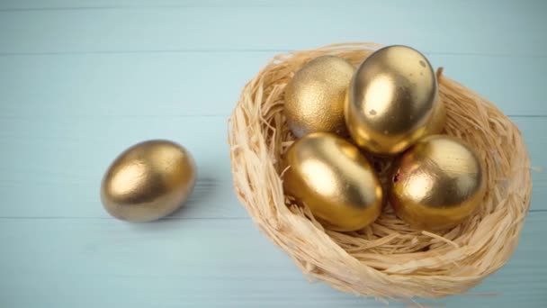 Easter eggs painted in gold color on blue wooden table close up