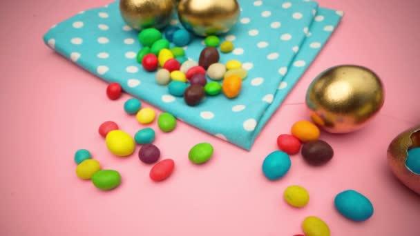 Zlatá vejce s roztroušenými sladkostmi na velikonoce na růžovém pozadí