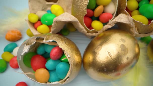 Golden decorative Easter eggs filled with colorful candies on wooden table close up
