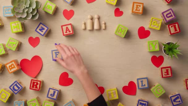 Woman hand arranging wooden cubes with word FAMILY top view