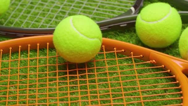 Tenisové míčky a raketa na zelené trávě pozadí zblízka