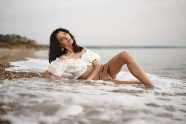 Young relaxed woman sitting all alone on empty beach