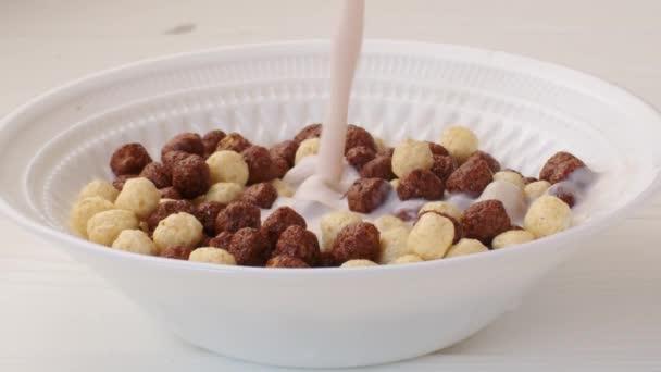 Mléko nalévání do misky s čokoládovými kuličkami cereálie k snídani