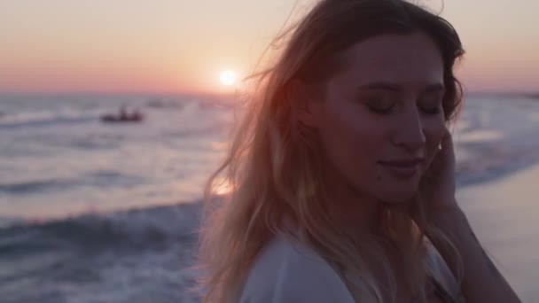 Young blonde woman with wavy hair standing on beach by the sea on sunset