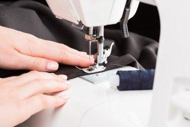 Women's hands behind her sewing