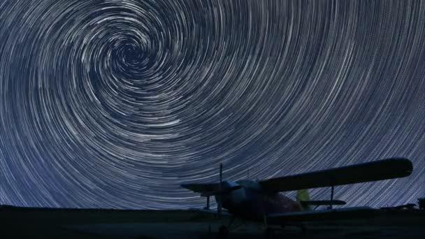 4 k hvězda stezky krásnou noční oblohu, spirálu hvězda stezky přes malé letiště osamělé letadlo. Vortex hvězda stezky. Malé letiště, osamělé letadlo v temné obloze