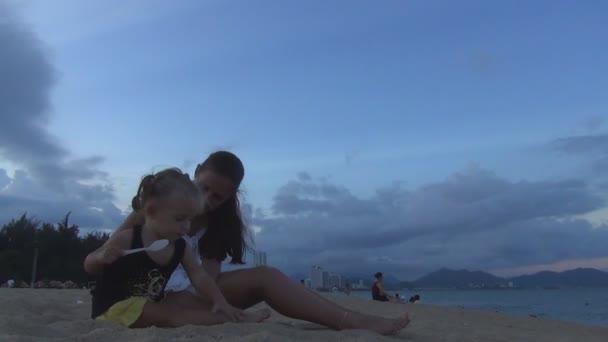 Maminka a dcera hraje s pískem na pláži. smějí se. Lechtání její dcera a matka písku nohy
