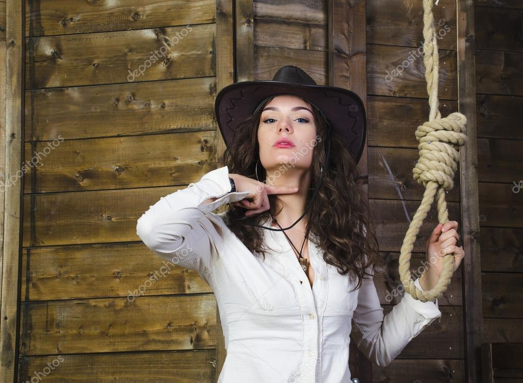 Girl cowboy near the gallows