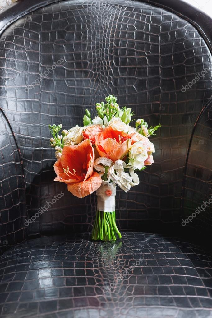Wedding bouquet on leather chair. Bride\'s traditional symbolic ...
