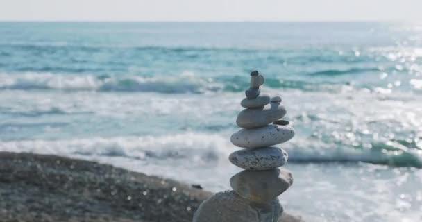 Pyramida z kamení na pláži. Hromada oblázků na skalnaté pláži na mořském surfování pozadí. Umělá struktura.