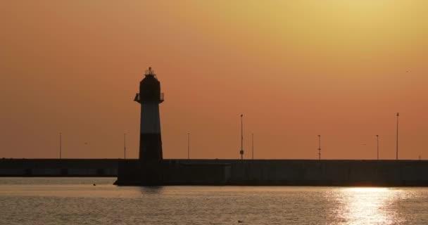Silhouette des Leuchtturms vor herrlichem Sonnenuntergang. Hafen von Sotschi, Russland.