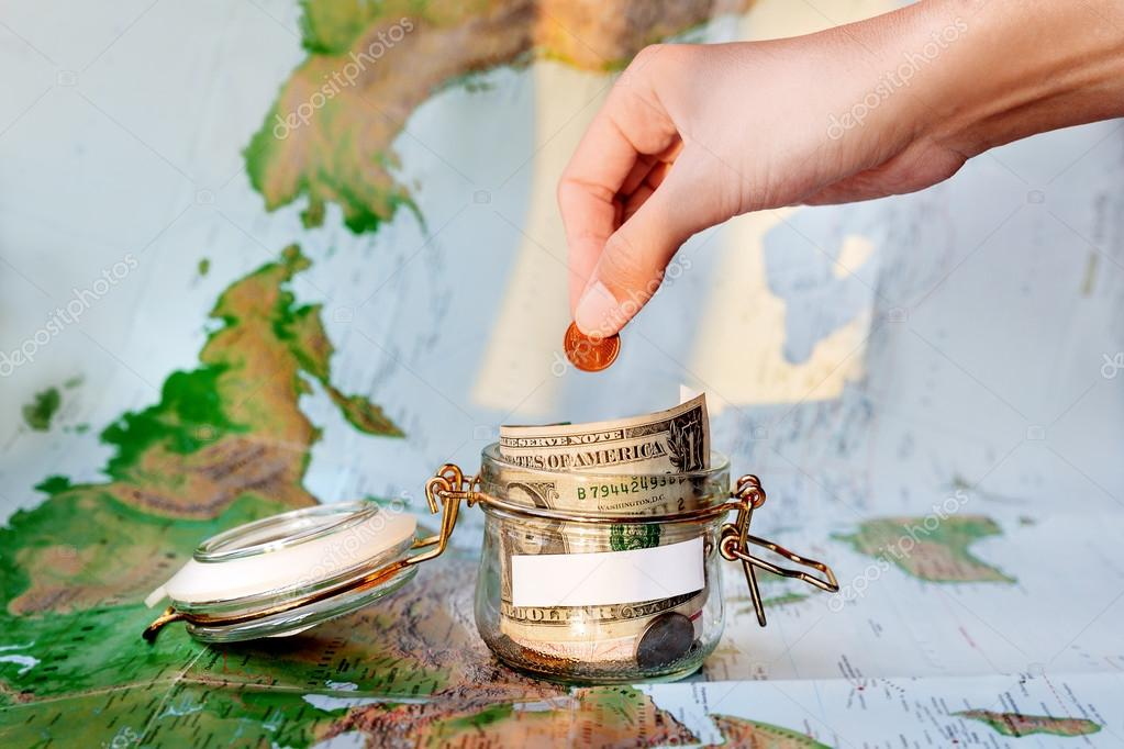 collecting money for travel glass tin as moneybox with cash savings