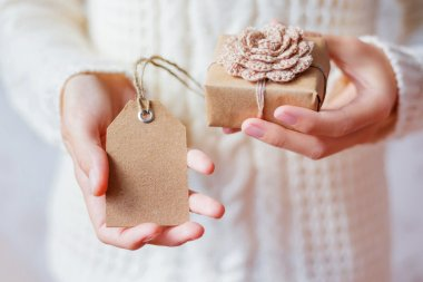 Woman in white knitted sweater holding a present. Gift is packed in craft paper with hand made crocheted flower.Empty tag for your text.