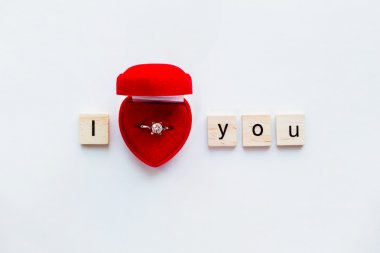 White background with wooden words I LOVE YOU and engagement ring