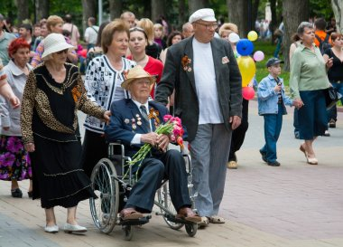 Volgograd, Russia - May 9, 2010: World War II veteran in a wheelchair and accompanied by relatives on Victory Day celebration on the Avenue of Heroes in Volgograd