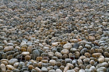 Stone wall in metal cage as background or texture