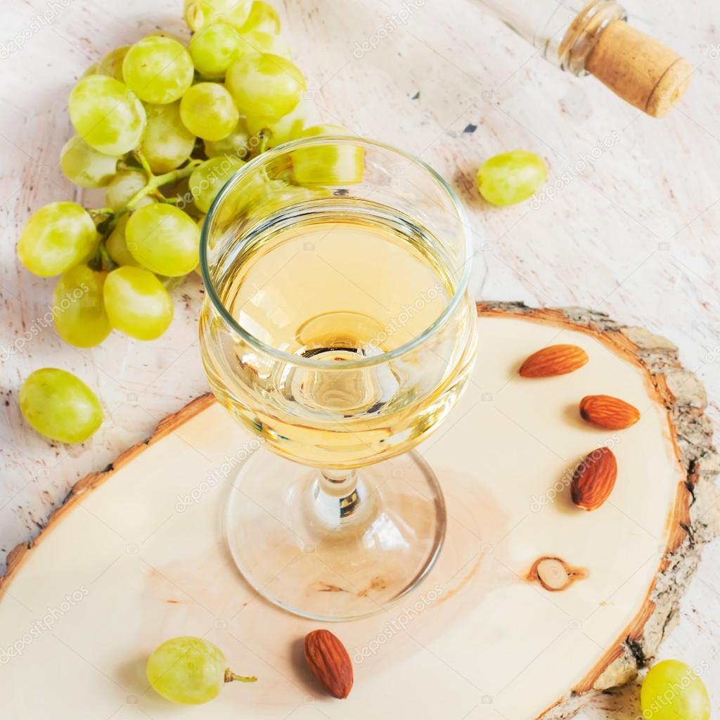 Vino en el vaso, las almendras y un racimo de uvas, coloreado blanco ...