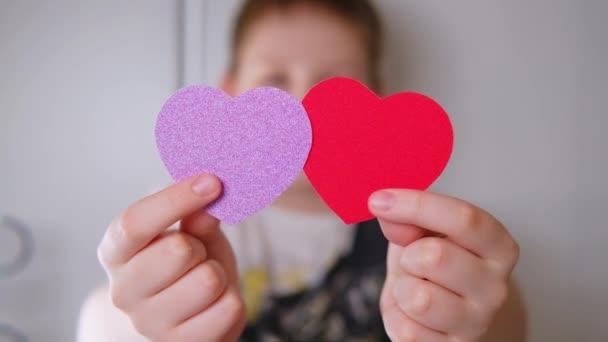 Červené a růžové srdce v rukou malého chlapce na Valentýna. Zpomalený pohyb.