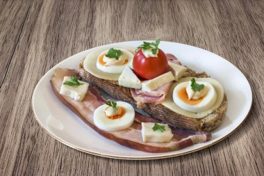 Bacon Cheese Egg Ham and Tomato Sandwich on Wooden Background