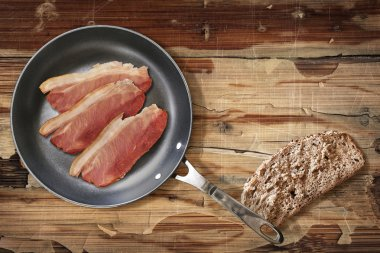 Fried Pork Ham rashers in Teflon Frying Pan with slice of Integral Bread on old Wooden Table