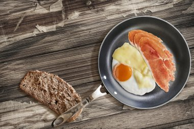 Prosciutto Rashers with Fried Egg and Cheese in Frying Pan with Bread Slice on Old Cracked Wooden Table