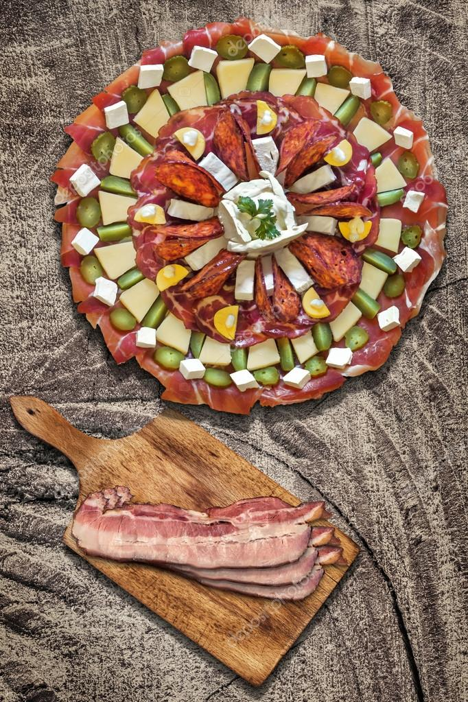 Appetizer Meze with Bacon Rashers on Cutting Board on Old Wood Background