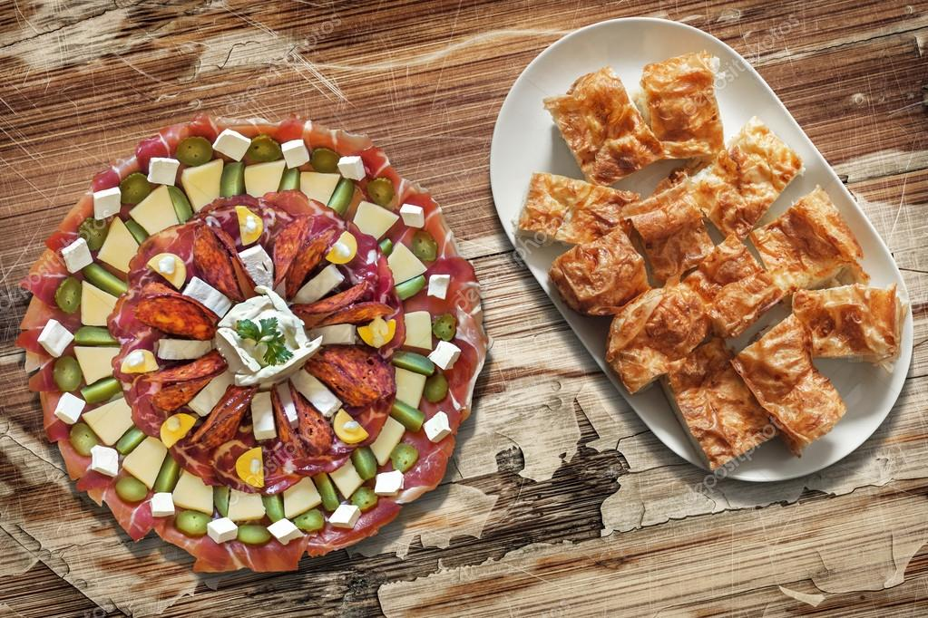 Plateful of Savory Appetizer Meze with Cheese Pie Gibanica Slices on Oblong Platter Placed on Old Wooden Backdrop