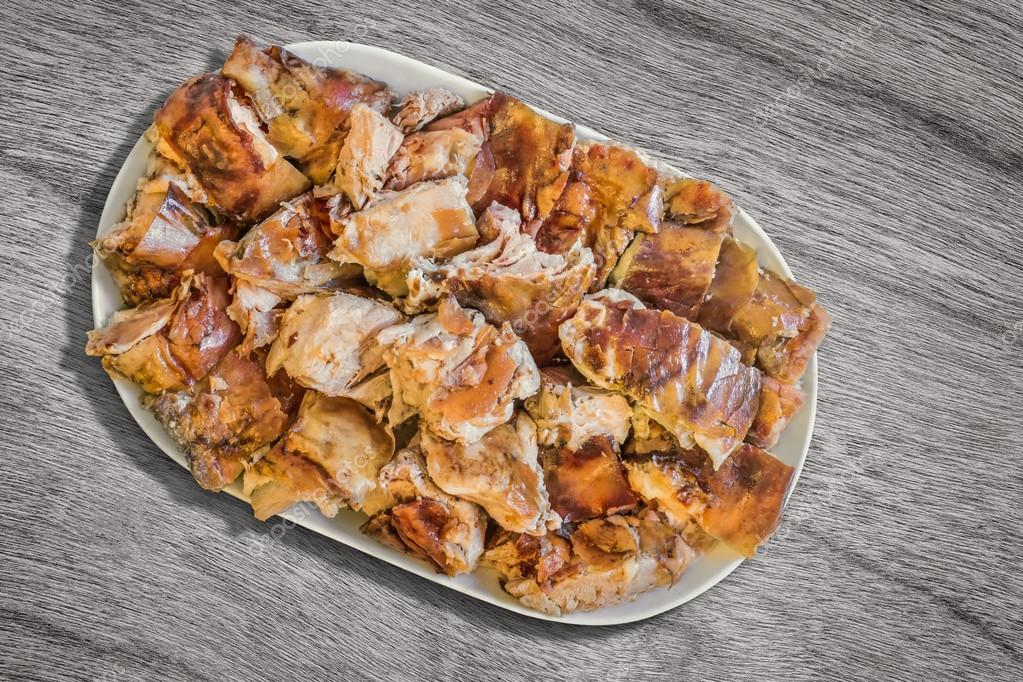 Plateful of Spit Roasted Pork Slices on Old Wooden Background