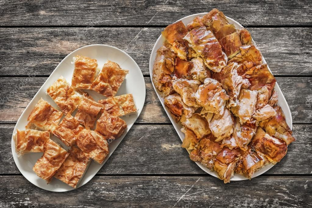 Platefuls of Cheese Pie Gibanica and Spit Roasted Pork Slices on Old Wooden Garden Table Surface