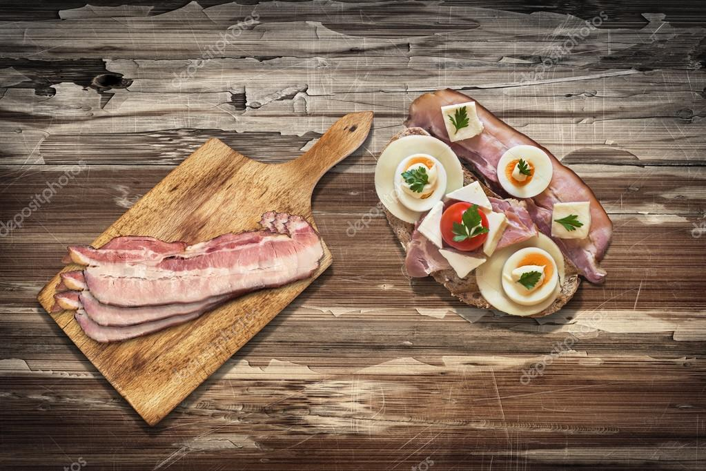 Ham Cheese and Tomato Sandwich with Bacon Rashers on Old Wooden Table Surface