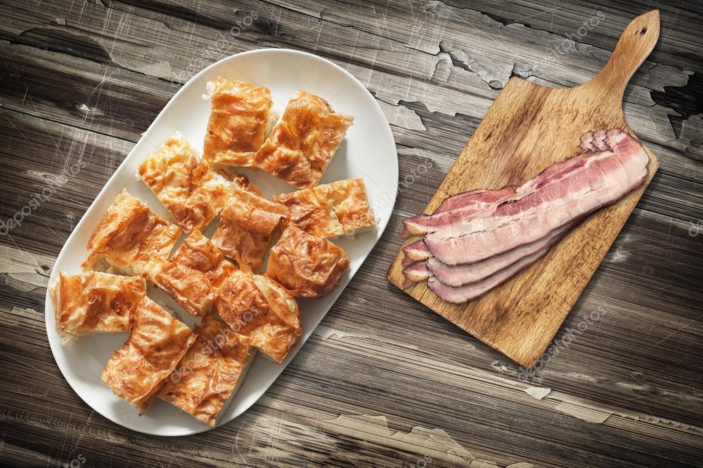 Platter of Cheese Pie Gibanica and Cutting Board with Pork Bacon Rashers Set on Old Wooden Garden Table Surface