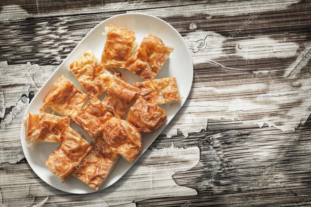 Plateful of Spit Roasted Pork Slices on Old Cracked Peeled Wooden Surface
