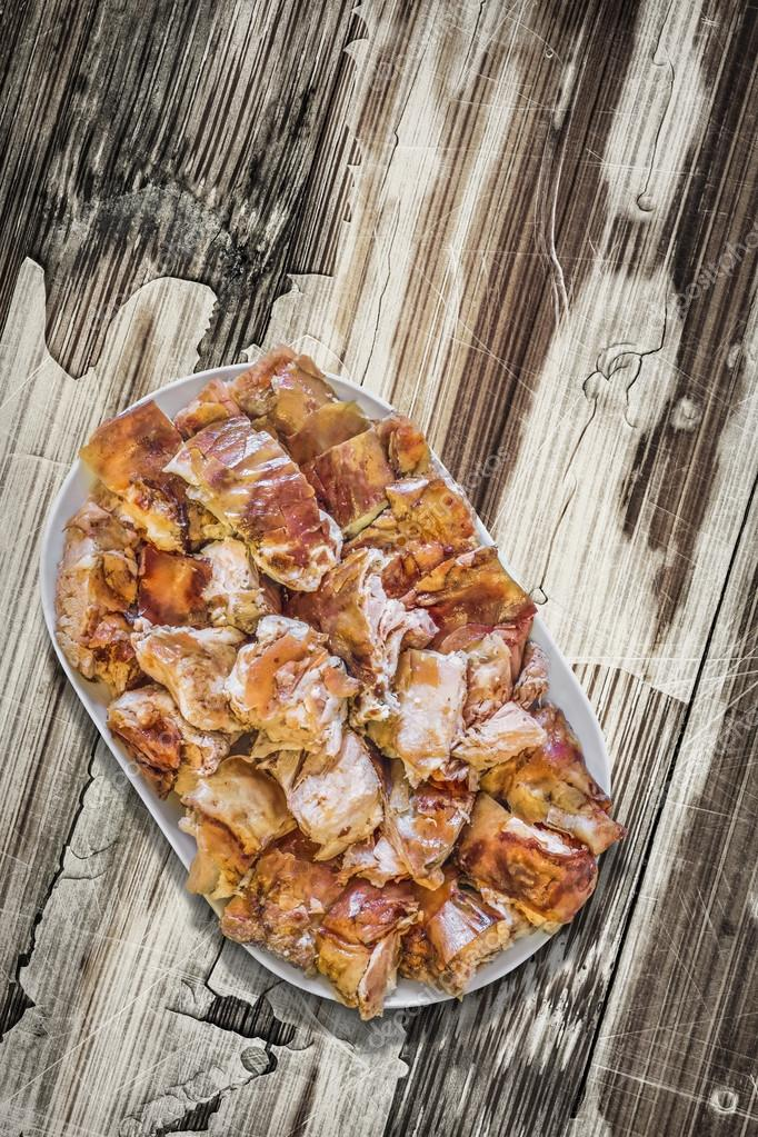 Plateful of Spit Roasted Pork Slices on Old Cracked Peeled Wooden Surface