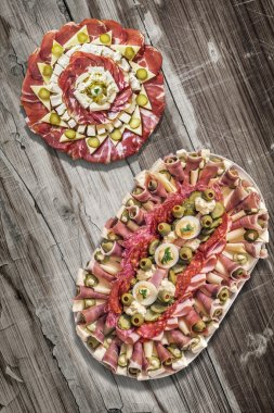 Two Platters of Savory Antipasto Meze Appetizers on Old Cracked Peeled Wooden Table