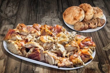 Plateful of Spit Roasted Pork with Baguette Integral Bread Slices and Pita Bread Loafs on Old Wooden Table