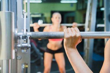 athlete girl holds metal barbell.