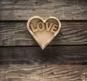 word Love inside wooden heart.