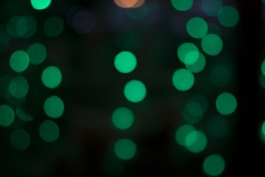 Green bokeh on a dark background.