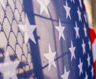 American flag behind fence